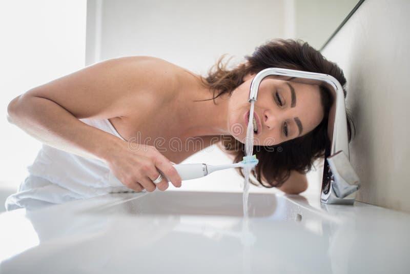 Довольно, средняя достигшая возраста женщина чистя ее зубы щеткой стоковое фото