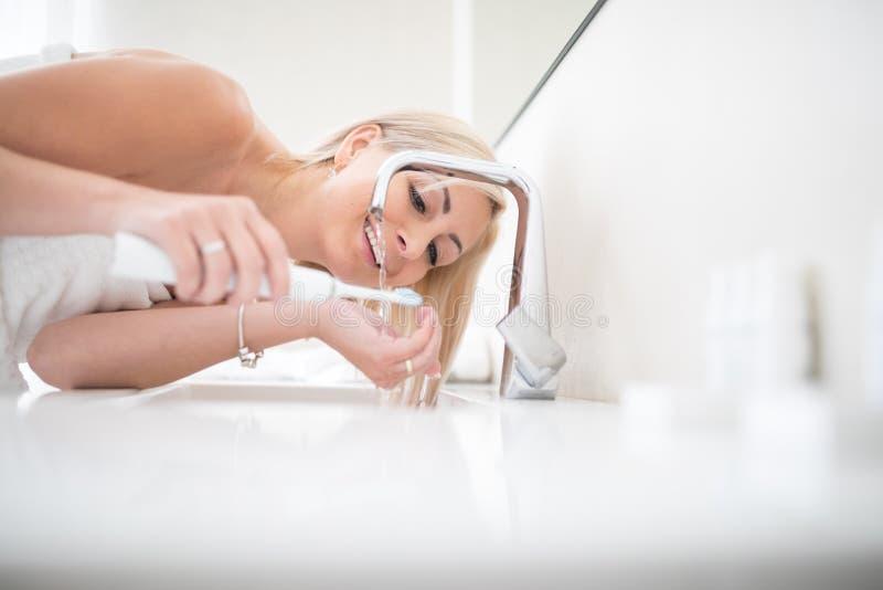 Довольно, средняя достигшая возраста женщина чистя ее зубы щеткой стоковые изображения