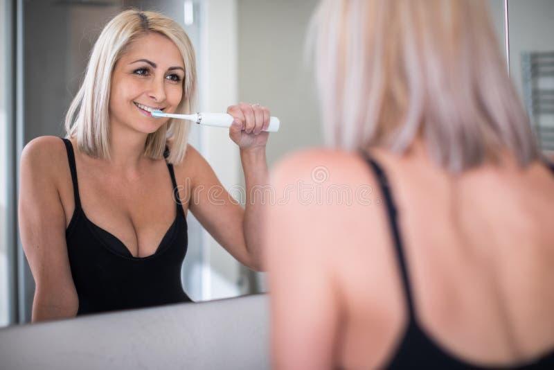 Довольно, средняя достигшая возраста женщина чистя ее зубы щеткой стоковая фотография rf