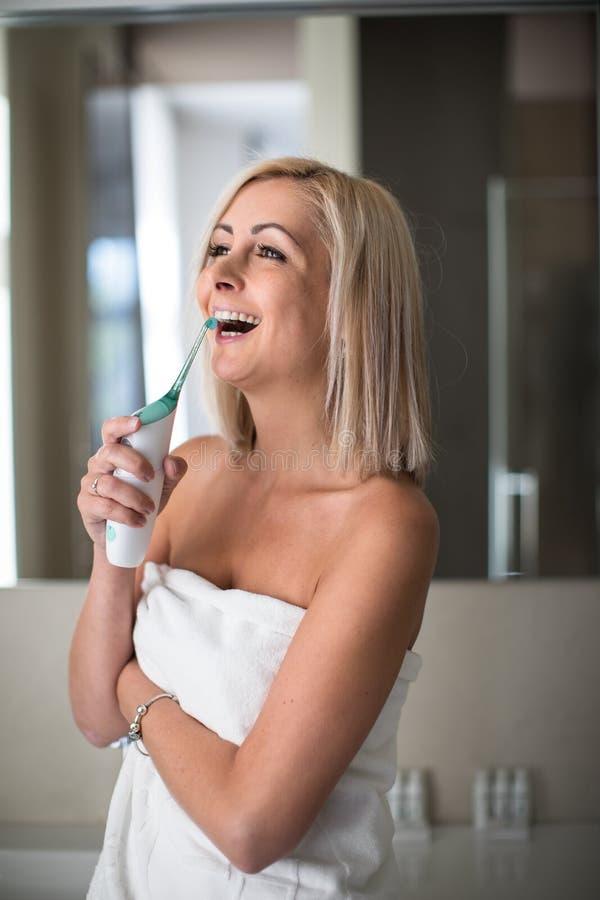 Довольно, средняя достигшая возраста женщина чистя ее зубы щеткой стоковое изображение rf