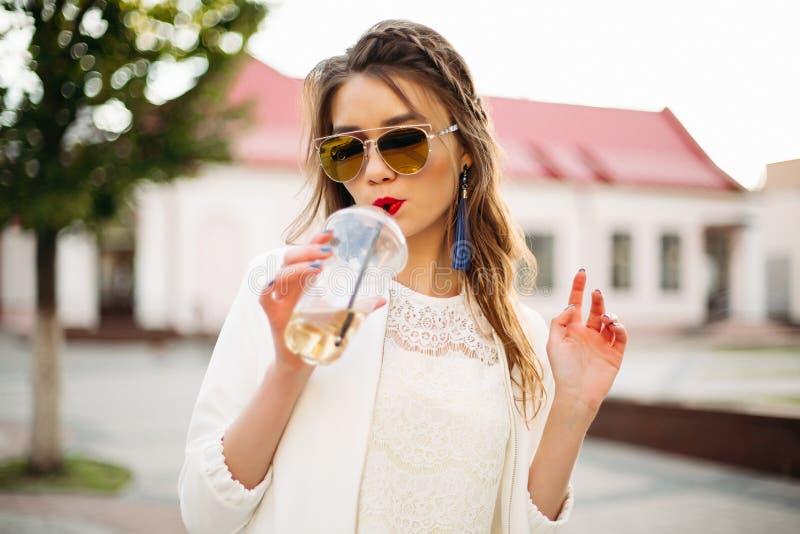 Довольно ультрамодная девушка с оплеткой в отраженных солнечных очках выпивая кофе в улице стоковое фото