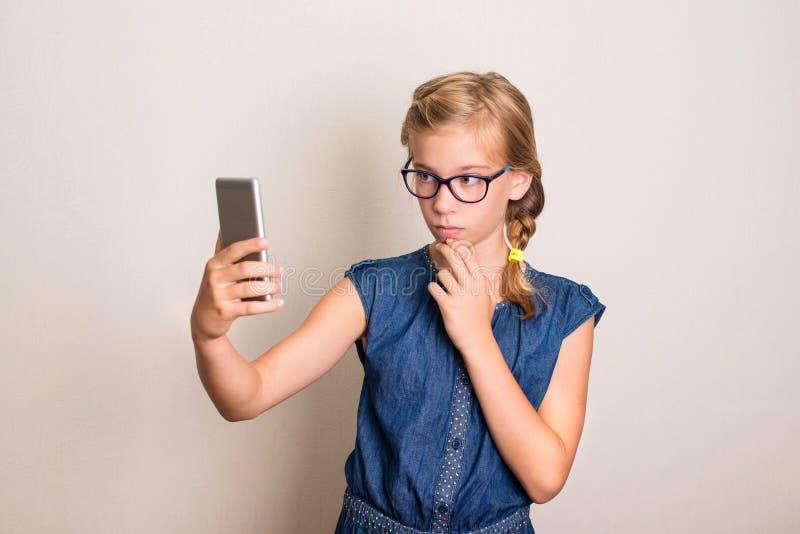 Довольно усмехаясь предназначенная для подростков девушка в стеклах делая фото selfie на умном стоковое фото rf