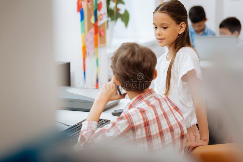 Довольно утомленная школьница смотря одноклассника стоковое изображение rf