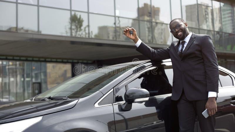 Довольный Афро-американский человек показывая ключ от нового роскошного автомобиля, мечты приходит верно стоковые изображения rf