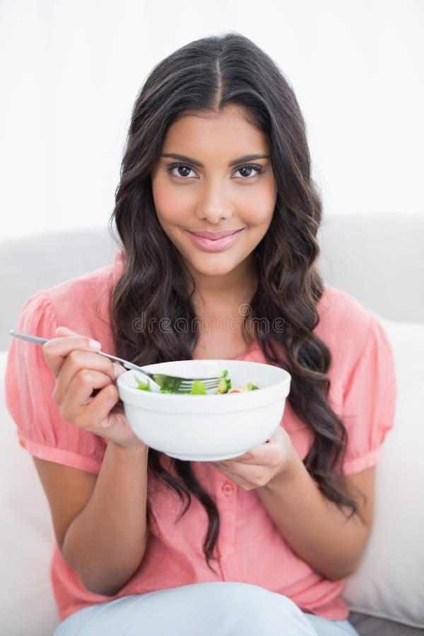 Довольное милое брюнет сидя на кресле держа салатницу стоковая фотография rf