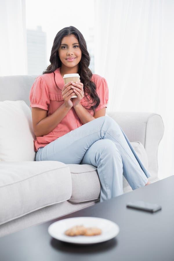 Довольное милое брюнет сидя на кресле держа устранимую чашку стоковые фото