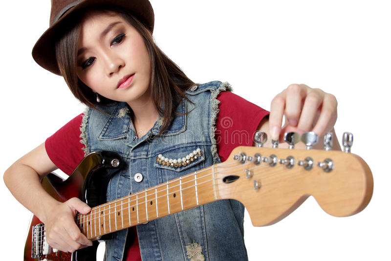 Довольно азиатская девушка настраивая ее гитару, на белой предпосылке стоковая фотография rf