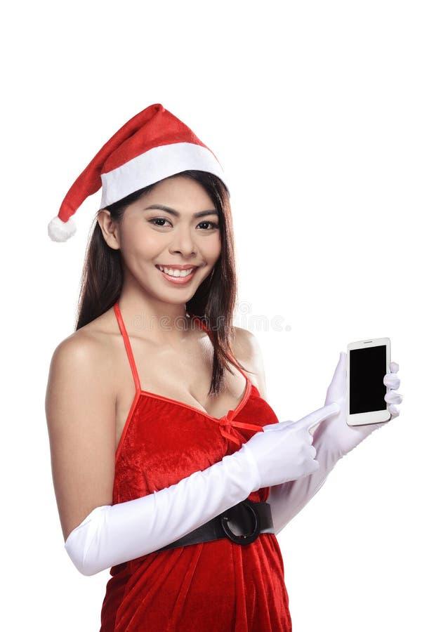 Довольно азиатская женщина в костюме Санта Клауса держа мобильный телефон стоковая фотография