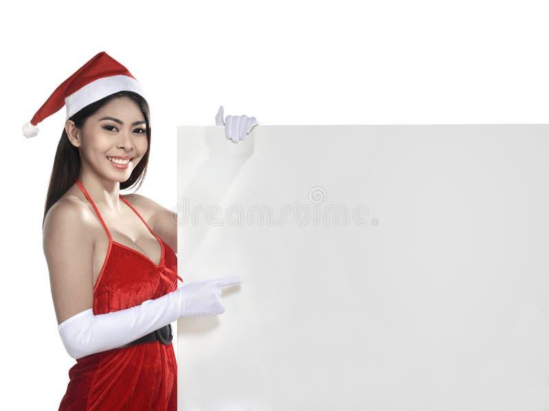 Довольно азиатская женщина нося костюм Санта Клауса держа пустую доску стоковое изображение rf