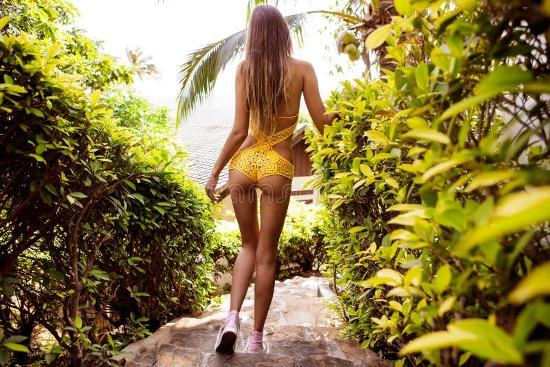Довольно атлетическая девушка в knit желтого бикини сексуальном на footpat стоковые изображения