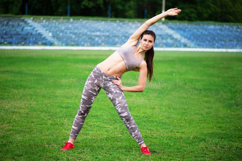 Довольно атлетическая девушка приниманнсяая за гимнастика стоковое изображение