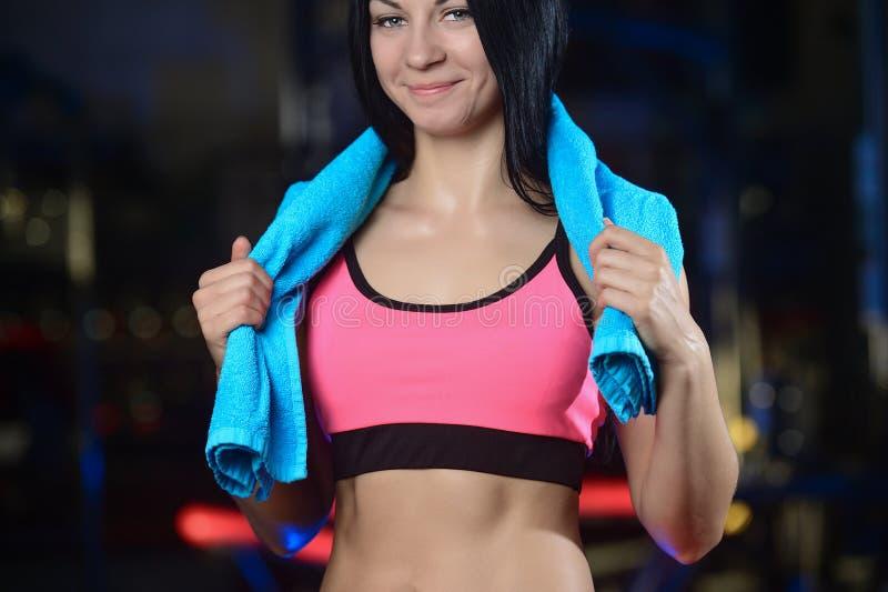 Довольно атлетическая женщина фитнеса с полотенцем в спортзале стоковые фотографии rf