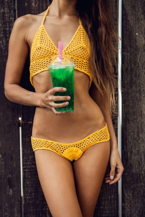 Довольно атлетическая молодая женщина в knit желтого бикини сексуальном около a стоковое фото rf