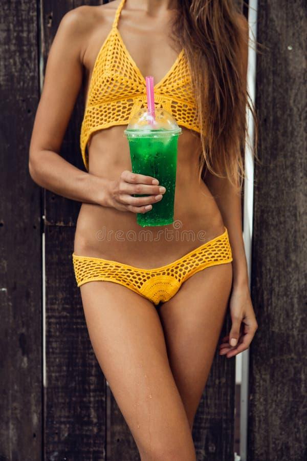 Довольно атлетическая молодая женщина в knit желтого бикини сексуальном около a стоковое фото