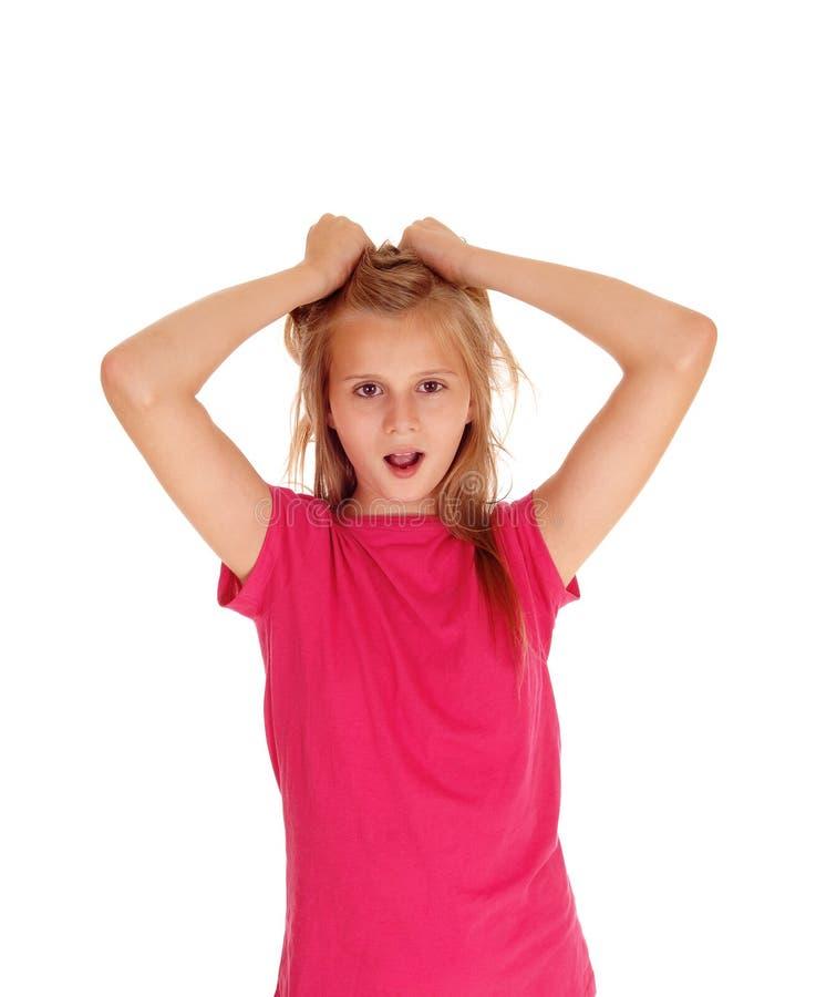 Довольно белокурая девушка вытягивая ее волосы стоковая фотография