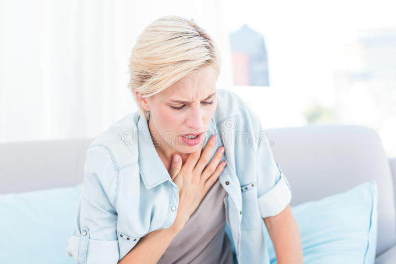 Довольно белокурая женщина имея затруднения дыхания стоковое фото