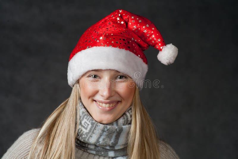 Довольно белокурая нося шляпа рождества на темноте стоковая фотография