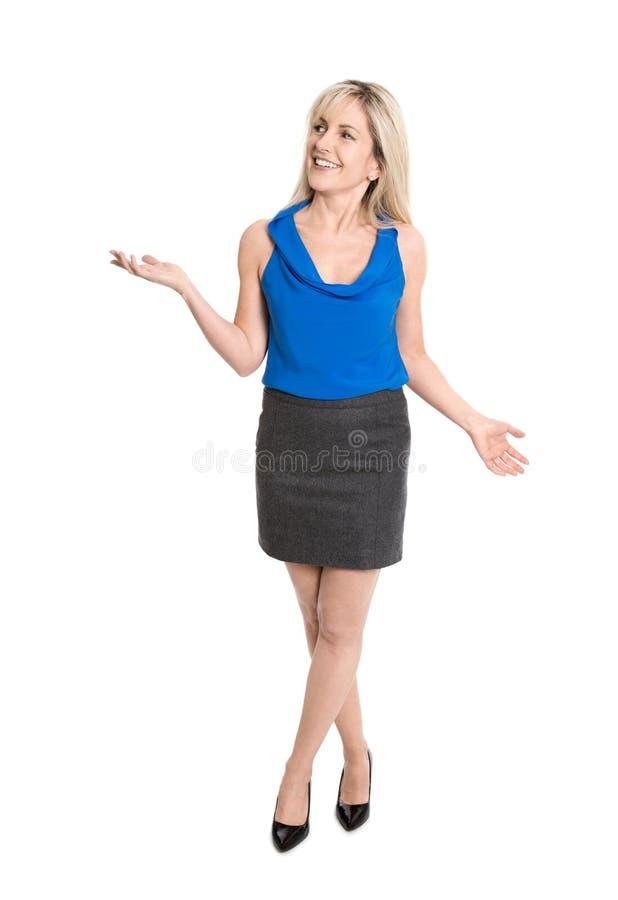 Довольно более старая изолированная женщина усмехаясь и показывать с ее руками стоковые изображения rf