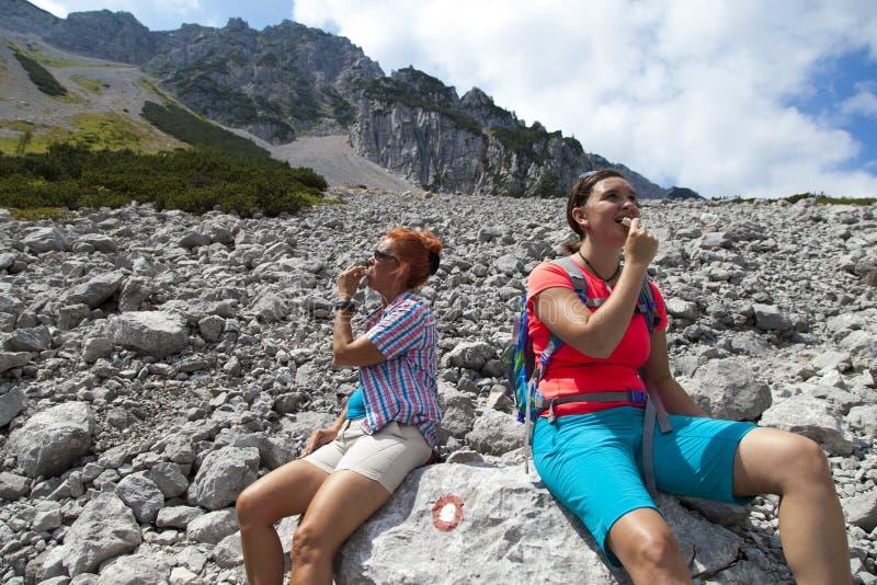 Довольно женские hikers есть бар muesli в горах, наслаждающся барами хлопьев granola, живя здоровый активный образ жизни в горе n стоковое изображение rf