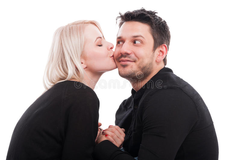 Довольно женский дающ поцелуй на щеке парня стоковое изображение