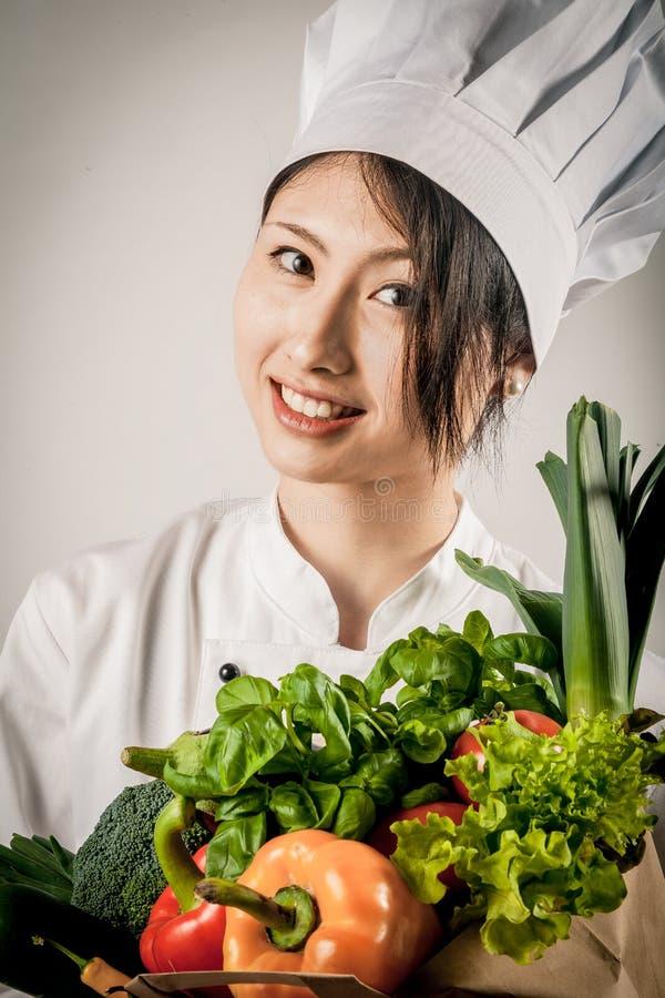 Довольно женский шеф-повар с свежими Veggies в бумажной сумке стоковая фотография rf
