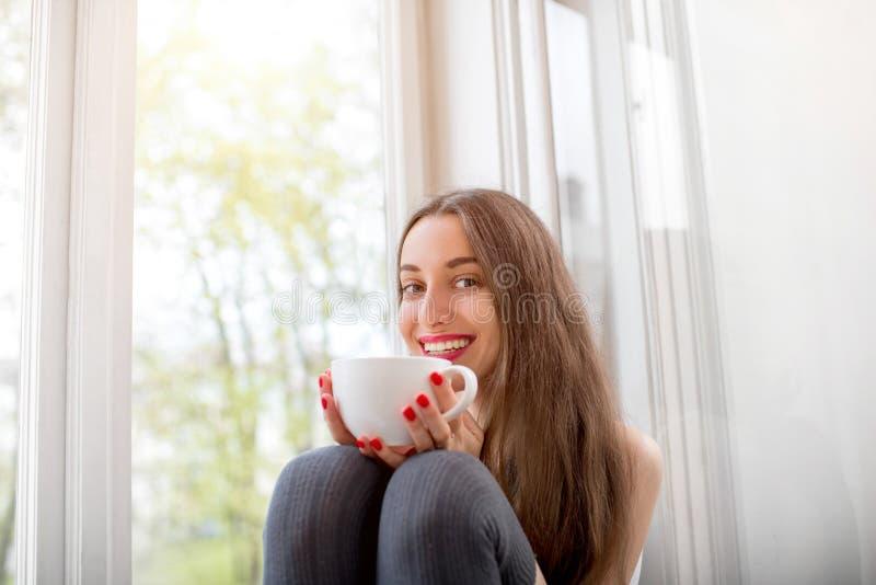 Довольно и усмехаясь девушка сидя около окна и смотря t стоковое изображение rf