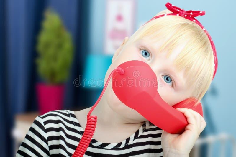 Довольно маленькая белокурая девушка с красным ретро телефоном стоковое изображение