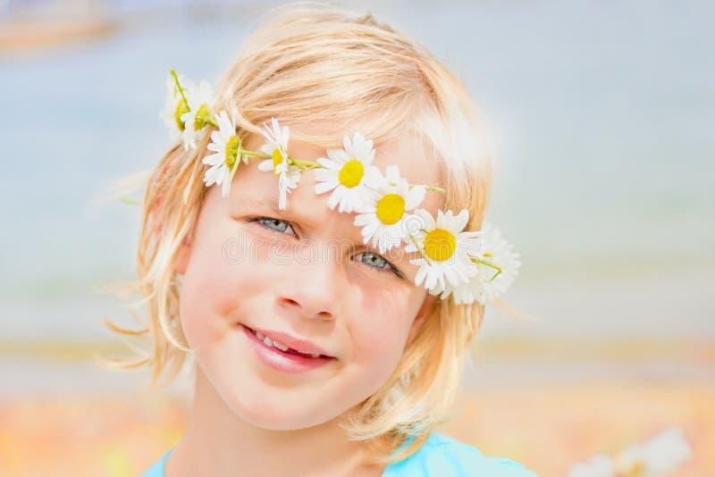 Довольно маленькая белокурая девушка с кроной маргариток стоковые изображения