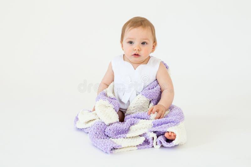 Довольно маленький ребёнок сидя на поле при изолированная шотландка стоковые фото