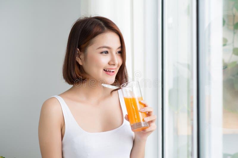 Довольно молодая азиатская женщина в светлой комнате выпивая апельсиновый сок стоковые фотографии rf