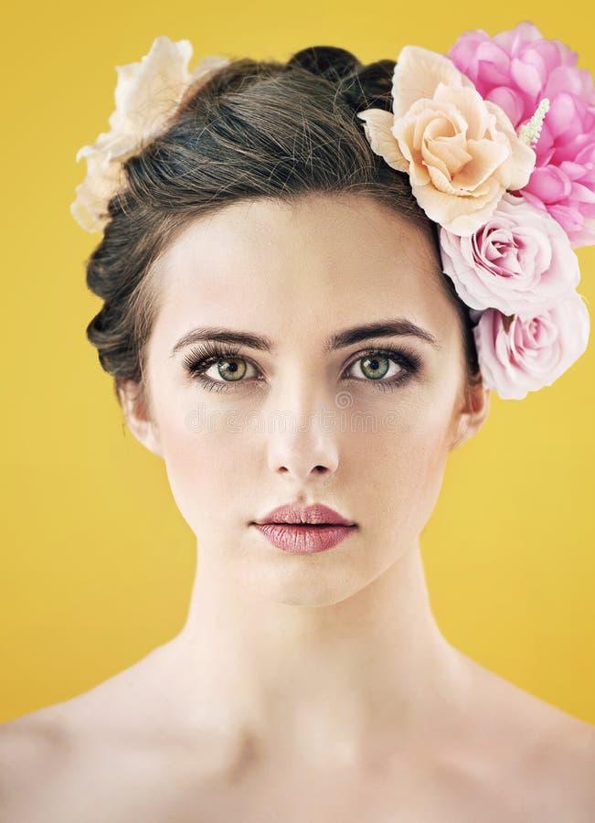 Довольно молодая дама с цветком положила в волосы стоковое изображение rf