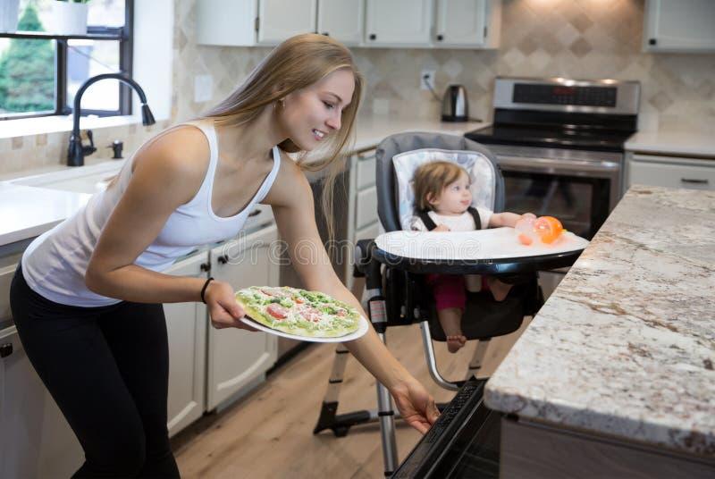 Довольно молодая белокурая женщина принимая очень вкусную пиццу из печи стоковые изображения rf