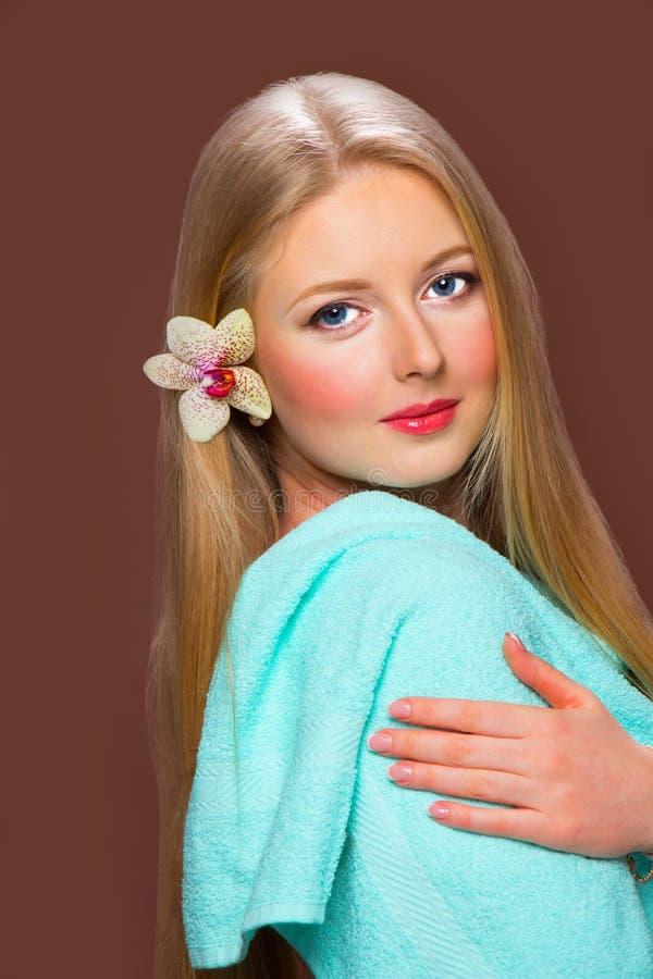 Довольно молодая белокурая женщина с красивыми волосами, голубым полотенцем и fl стоковая фотография