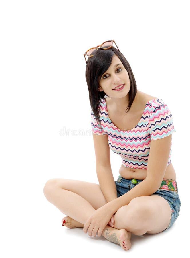 Довольно молодая женщина брюнет сидя положив ногу на ногу на белизне стоковые фотографии rf