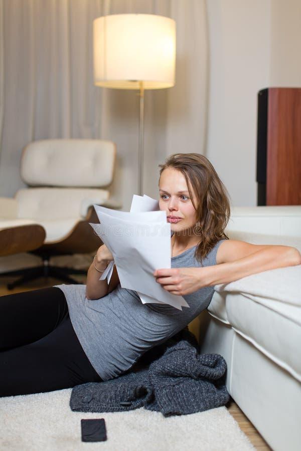 Довольно, молодая женщина идя через некоторую обработку документов в ее симпатичном l стоковая фотография