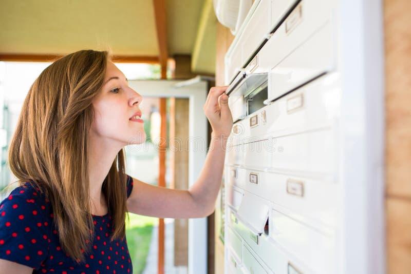 Довольно, молодая женщина проверяя ее почтовый ящик стоковое изображение