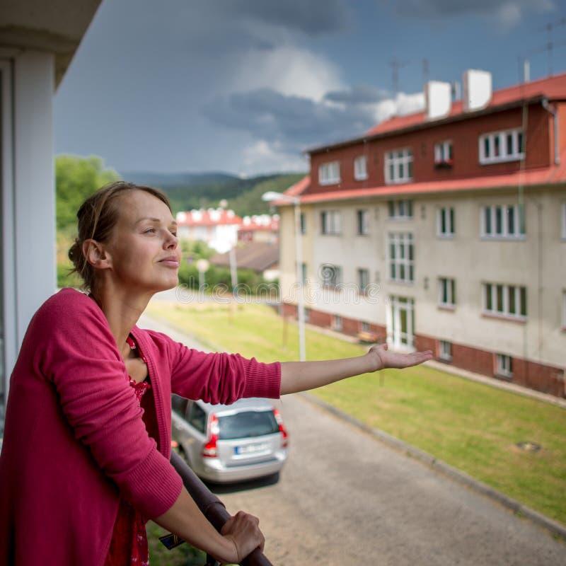 Довольно, молодая женщина проверяя идет дождь ли оно уже стоковые изображения