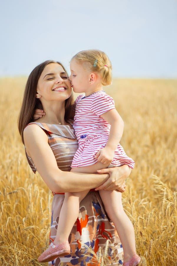Довольно молодая мать с дочерью счастлива в солнечном дне стоковые изображения rf