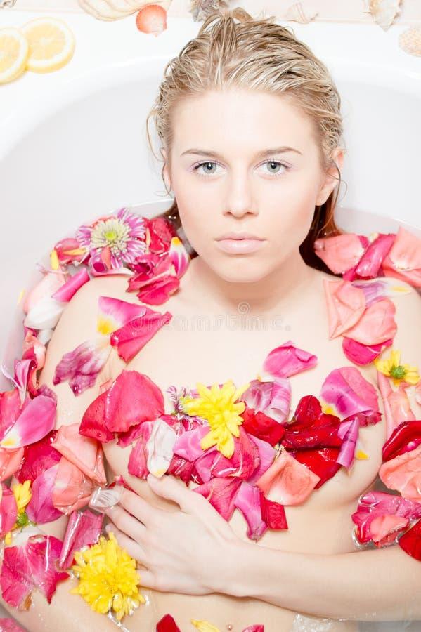 Красивейшая белокурая дама принимая ванну с лепестками цветка стоковая фотография