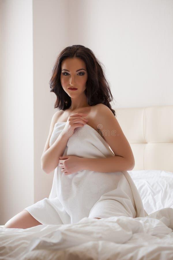 Довольно молодое брюнет отдыхая в спальне гостиницы стоковые фото