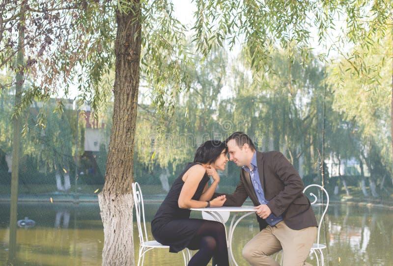 Довольно молодые любящие пары сидя в кафе тротуара совместно стоковые фотографии rf