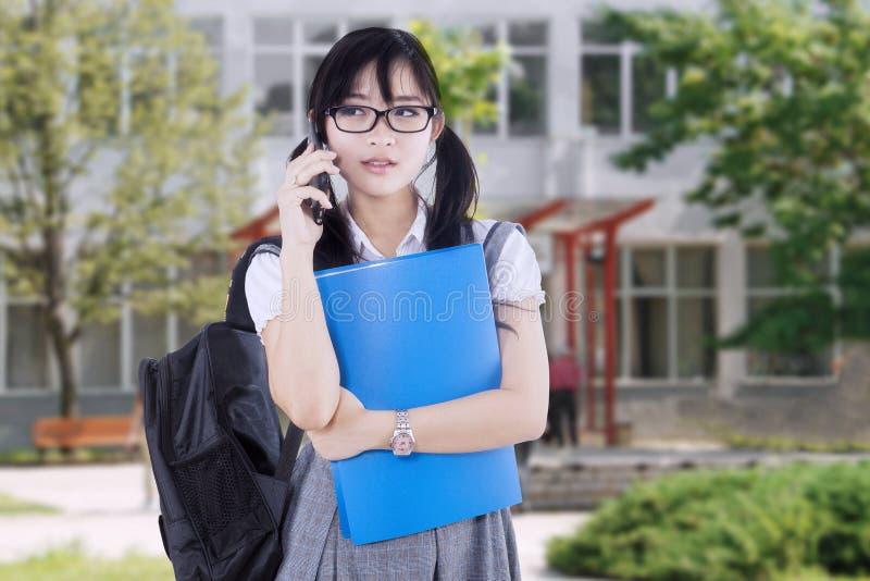 Довольно подростковый студент говоря на телефоне стоковые фото