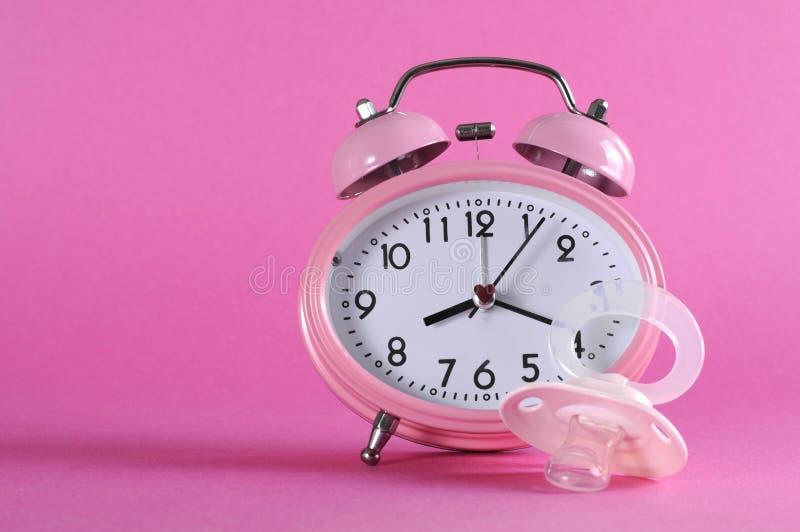 Довольно розовый винтажный ретро будильник стиля с pacificer куклы младенца стоковая фотография