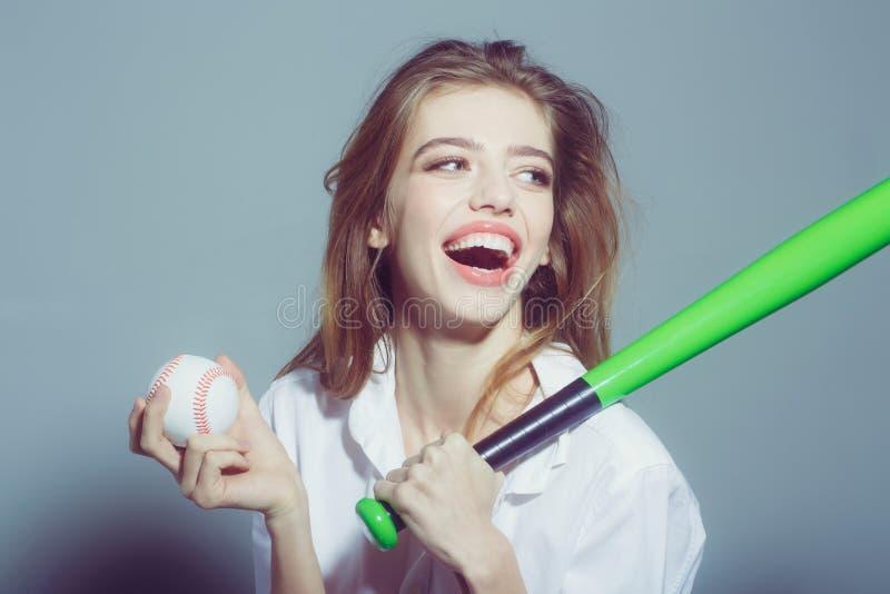 Довольно сексуальная женщина с длинными волосами держит зеленую бейсбольную биту стоковая фотография rf