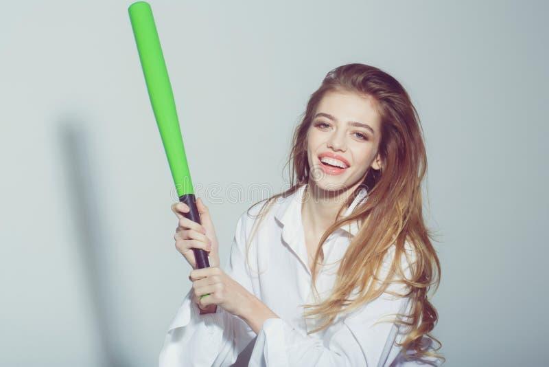 Довольно сексуальная женщина с длинными волосами держит зеленую бейсбольную биту стоковые фотографии rf