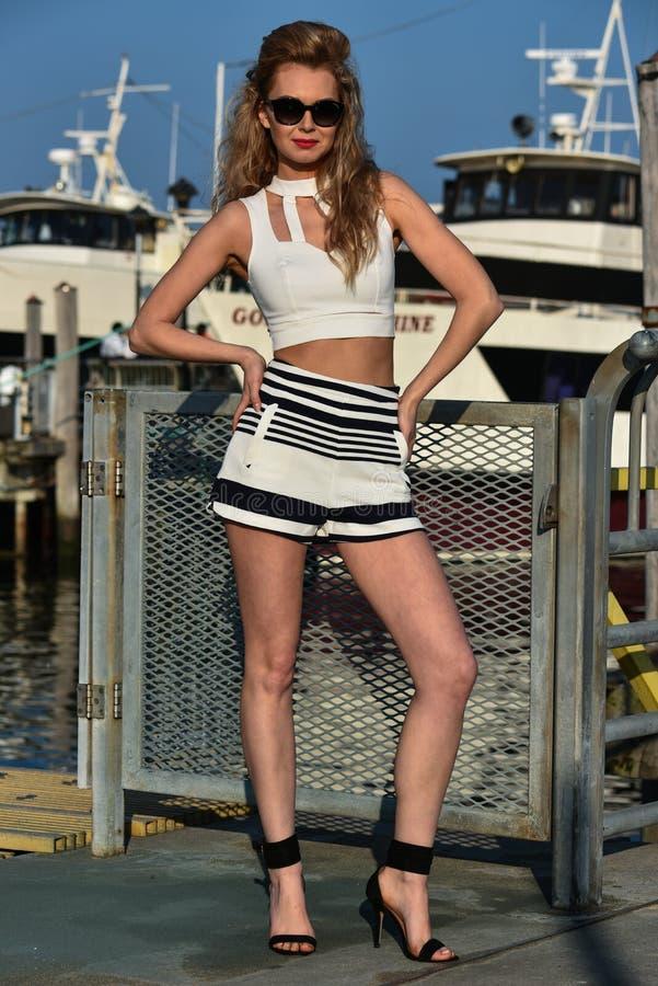 Довольно стильная молодая женщина в шортах, верхней части и солнечных очках матроса представляя довольно на пристани стоковые изображения