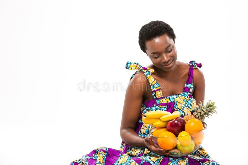 Довольно счастливая африканская женщина сидя и смотря свежие фрукты стоковое фото