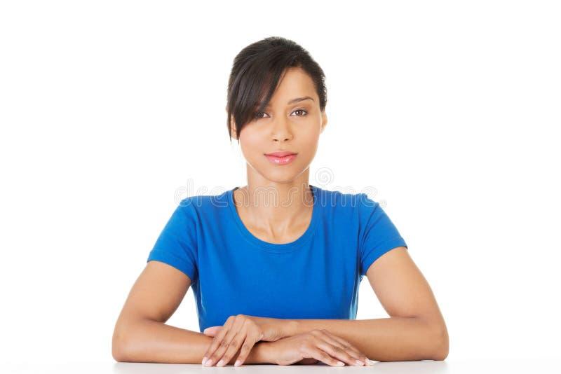 Довольно, счастливый, молодая женщина в вскользь одеждах сидя на столе стоковое изображение rf