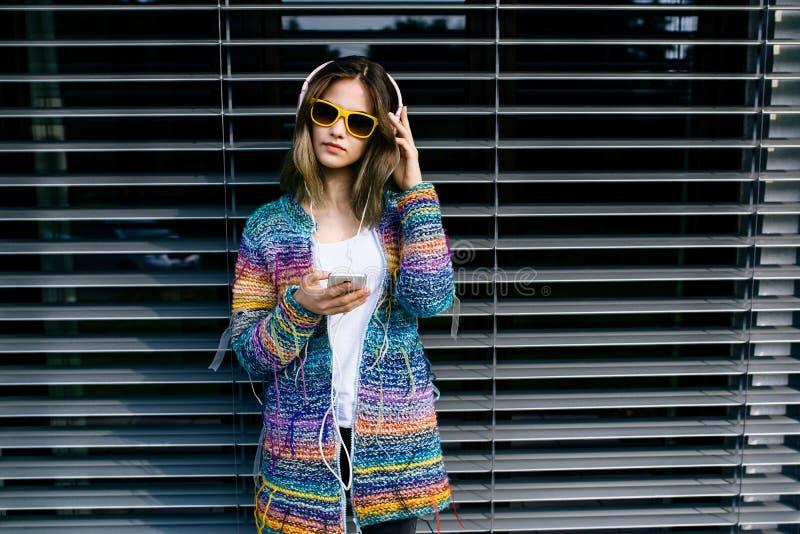 Довольно холодная девушка в иметь потеху и слушает к музыке стоковая фотография rf