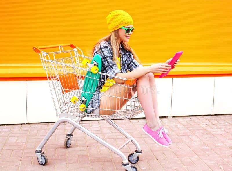 Довольно холодная девушка используя ПК таблетки чтения в тележке вагонетки покупок над красочным апельсином стоковое фото